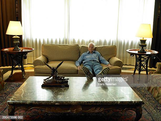 senior man relaxing on sofa, propping feet on table - old man feet stock pictures, royalty-free photos & images