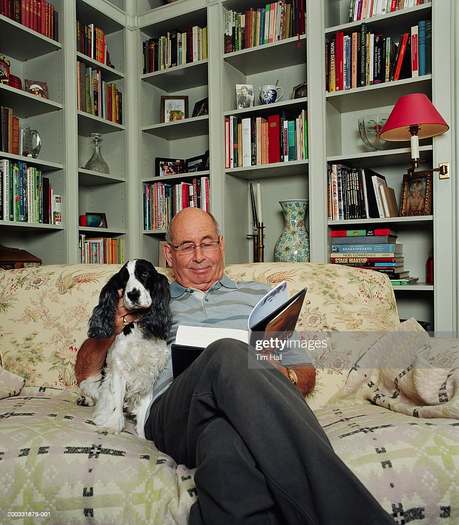 Senior man relaxing on sofa, reading book and petting dog, smiling : Stock Photo