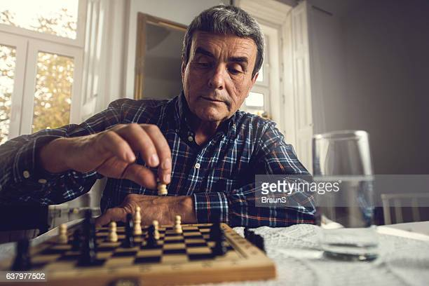 Senior man relaxing while playing chess at home.