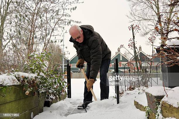Senior man removes snow