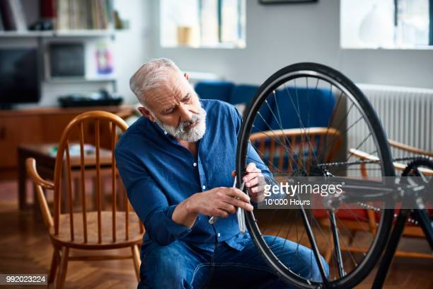 senior man removing bicycle tyer to repair a puncture - taking off activity stock pictures, royalty-free photos & images