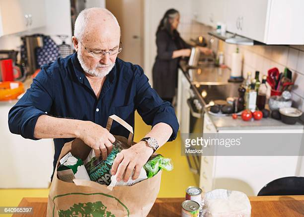 Senior man removing grocery from shopping bag while woman working in kitchen