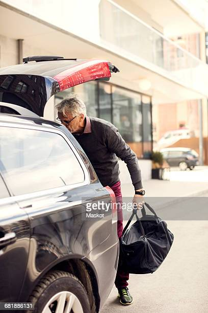 Senior man removing luggage from car trunk while standing in city
