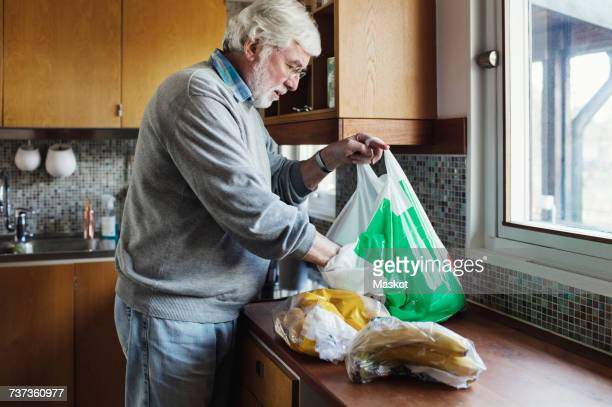 Senior man removing packets from plastic bag at kitchen counter