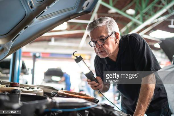 senior man repairing a car in auto repair shop - working seniors stock pictures, royalty-free photos & images