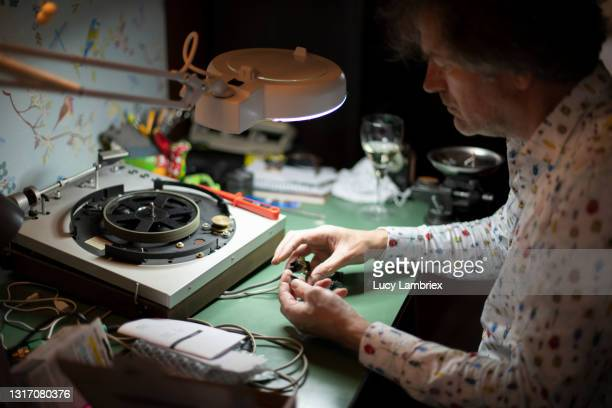 senior man repairing an old turntable at home - north holland stock pictures, royalty-free photos & images
