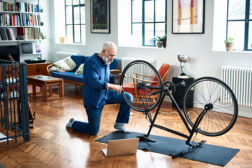 Senior man repairing bicycle on floor in apartment - gettyimageskorea