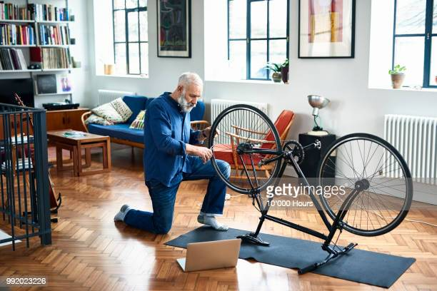 Senior man repairing bicycle on floor in apartment