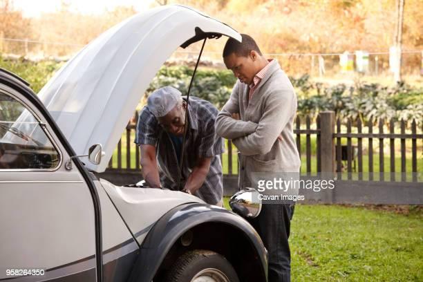 Senior man repairing car by son standing on grassy field