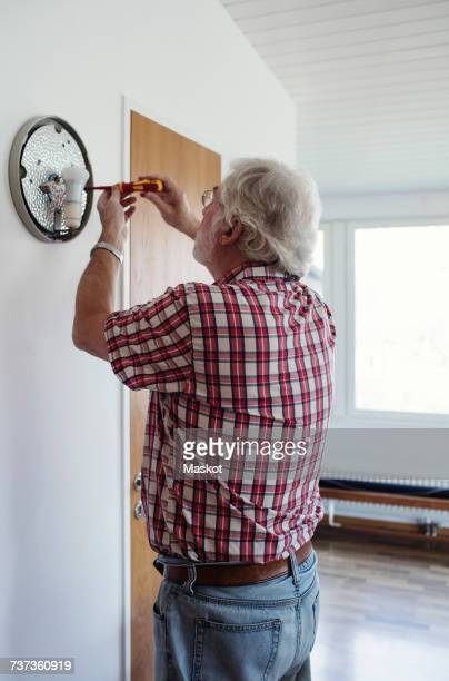 Senior man repairing sconce on white wall at home