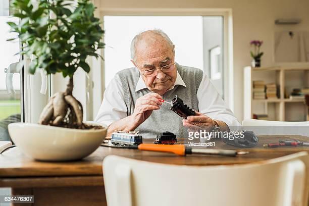 senior man repairing toy train at home - 模型の汽車 ストックフォトと画像