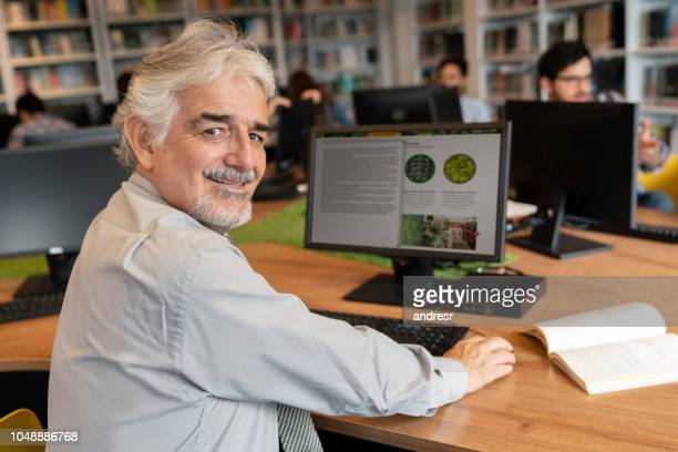 senior man researching online at a library - old university stock pictures, royalty-free photos & images