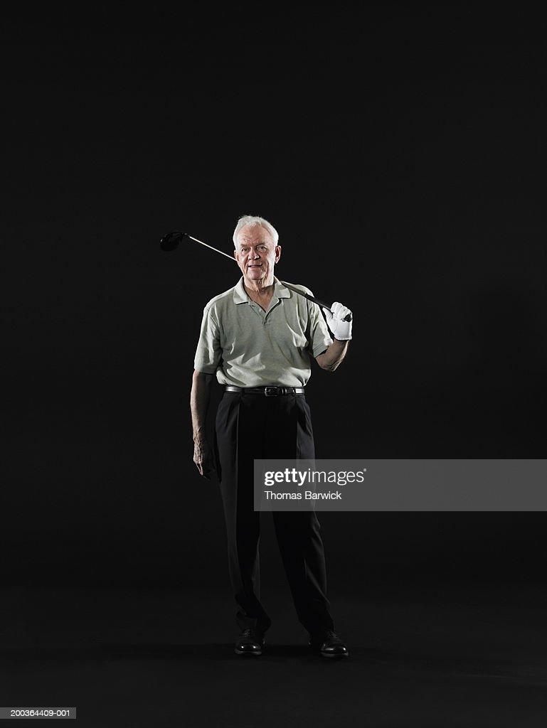 Senior man resting golf club on shoulder, portrait : Stock Photo