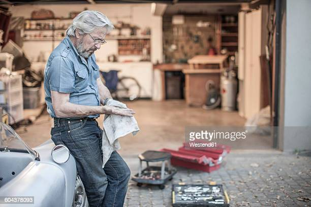 Senior man restoring a car