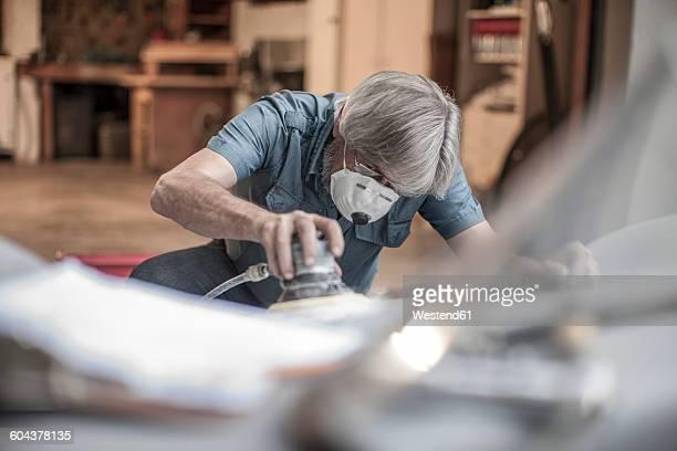 Senior man restoring a car