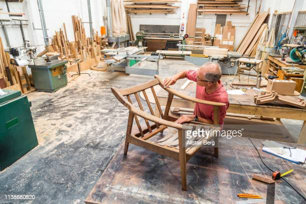 senior man restoring an old chair in a woodworking studio - furniture stock pictures, royalty-free photos & images