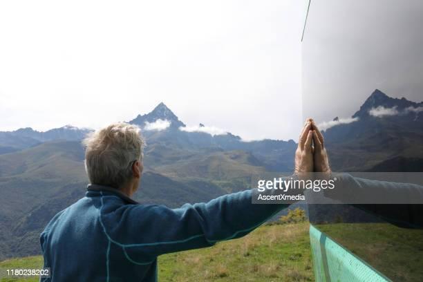 el hombre mayor descansa contra la furgoneta camper en la pradera de montaña - 55 59 años fotografías e imágenes de stock