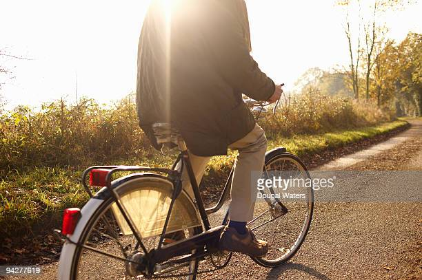 Senior man riding bicycle in countryside.