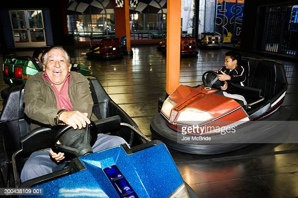 Senior man riding bumper car at amusement park