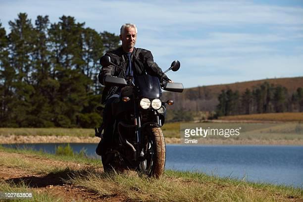 Senior man riding motorcycle next to lake