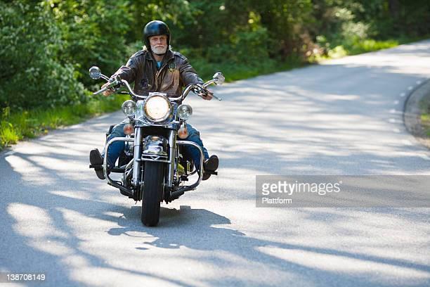 Senior man riding vintage motorbike