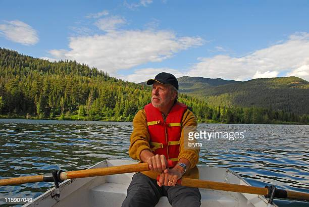 Senior man rowing  on Tyaughton Lake, Goldbridge,British Columbia,Canada.