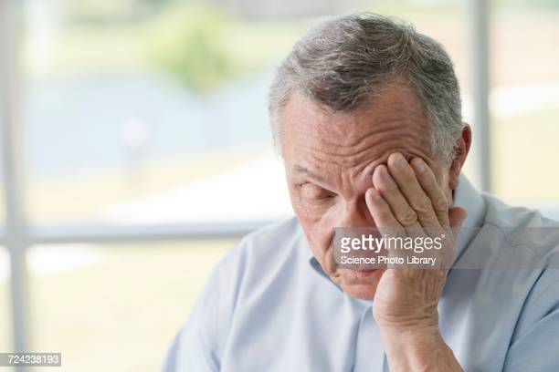 senior man rubbing face - medical condition stock pictures, royalty-free photos & images