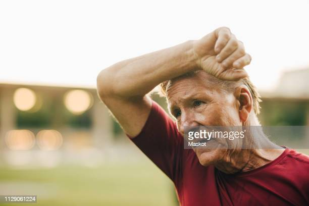 senior man rubbing face while sweating during workout at park - exhaustion stock pictures, royalty-free photos & images