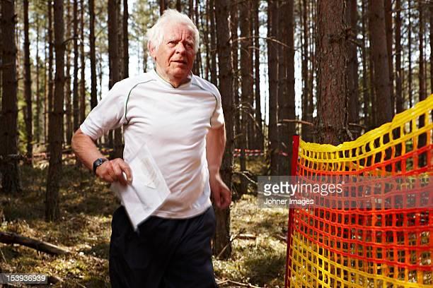 Senior man running in forest