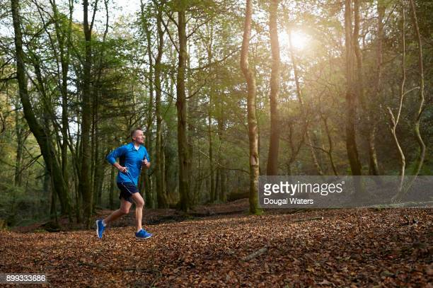senior man running in woodland. - one mature man only stock pictures, royalty-free photos & images
