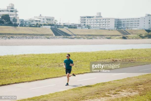 senior man running or jogging in a park in the city - 気が若い ストックフォトと画像