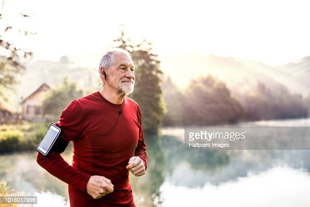 senior man running outdoors by the lake, a smart phone in an arm band. - watch what happens: live stock-fotos und bilder