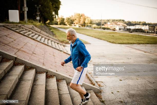 senior man running. - steps stock pictures, royalty-free photos & images