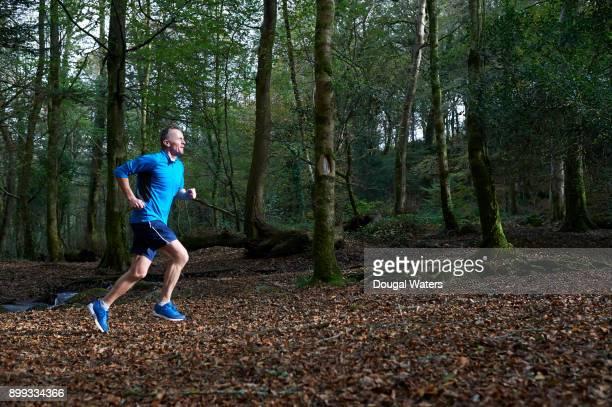 senior man running through woodland. - 55 59 jahre stock-fotos und bilder