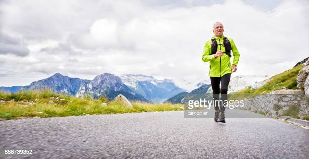 senior hombre corriendo camino de alta montaña con picos de fondo - black pants fotografías e imágenes de stock