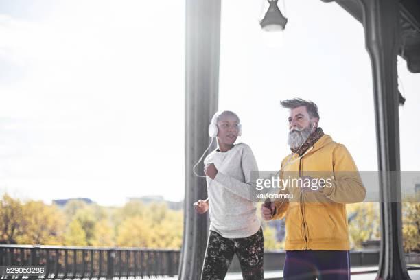 senior hombre corriendo con su entrenador personal en parís - pareja hombre mayor y mujer joven fotografías e imágenes de stock