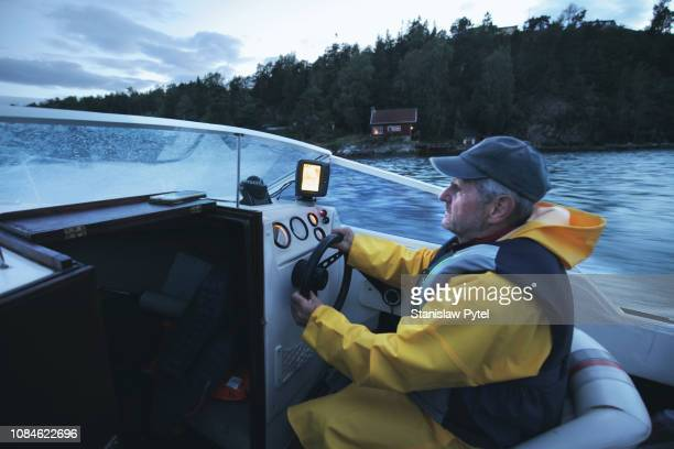 senior man sailing on boat at night - life jacket stock pictures, royalty-free photos & images