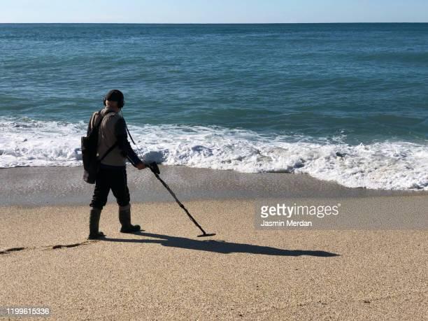 senior man searching for gold with metal detector on beach - vinden stockfoto's en -beelden