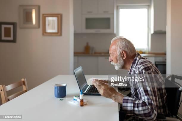 senior man online zoeken over geneeskunde - medicijnen innemen stockfoto's en -beelden