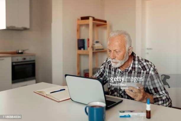 homme aîné recherchant en ligne au sujet de la médecine - medicare photos et images de collection