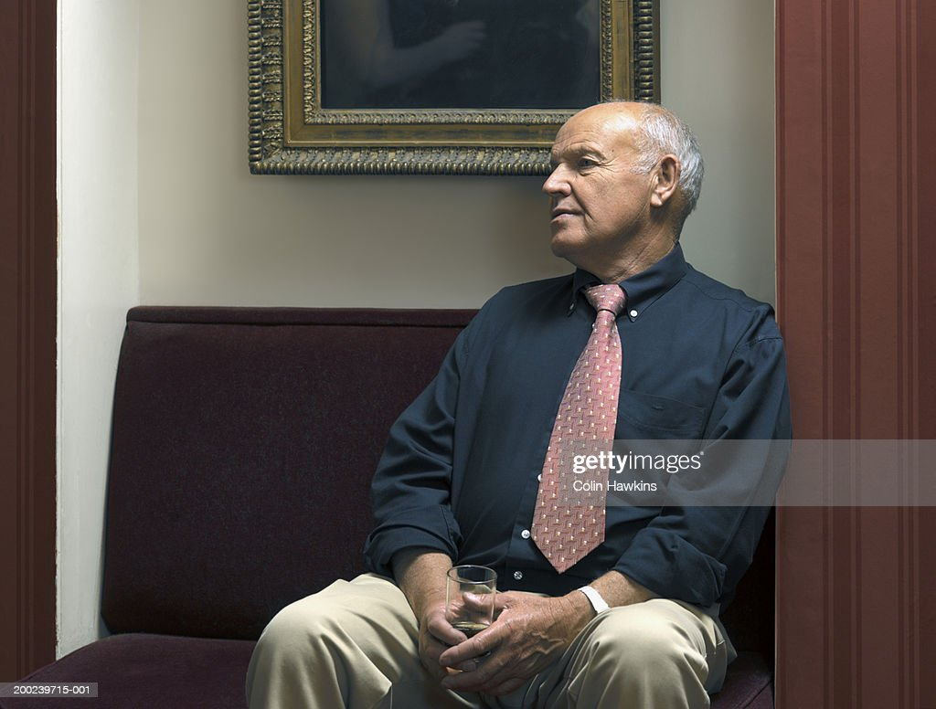 Senior man seated in theatre foyer, holding wine glass : Stock Photo