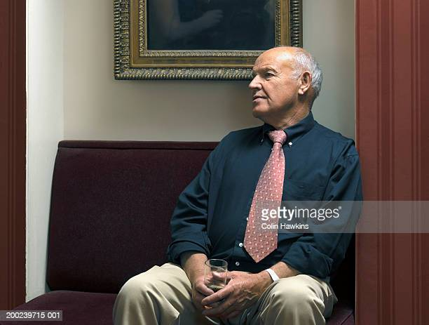 senior man seated in theatre foyer, holding wine glass - colin hawkins stock pictures, royalty-free photos & images