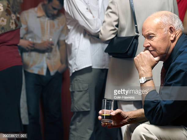 senior man seated in theatre foyer, holding wine glass, side view - intermission stock pictures, royalty-free photos & images