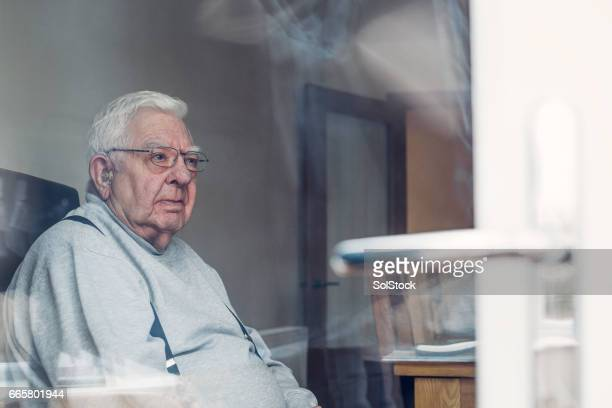 senior man seen through a window - pancia gonfia foto e immagini stock