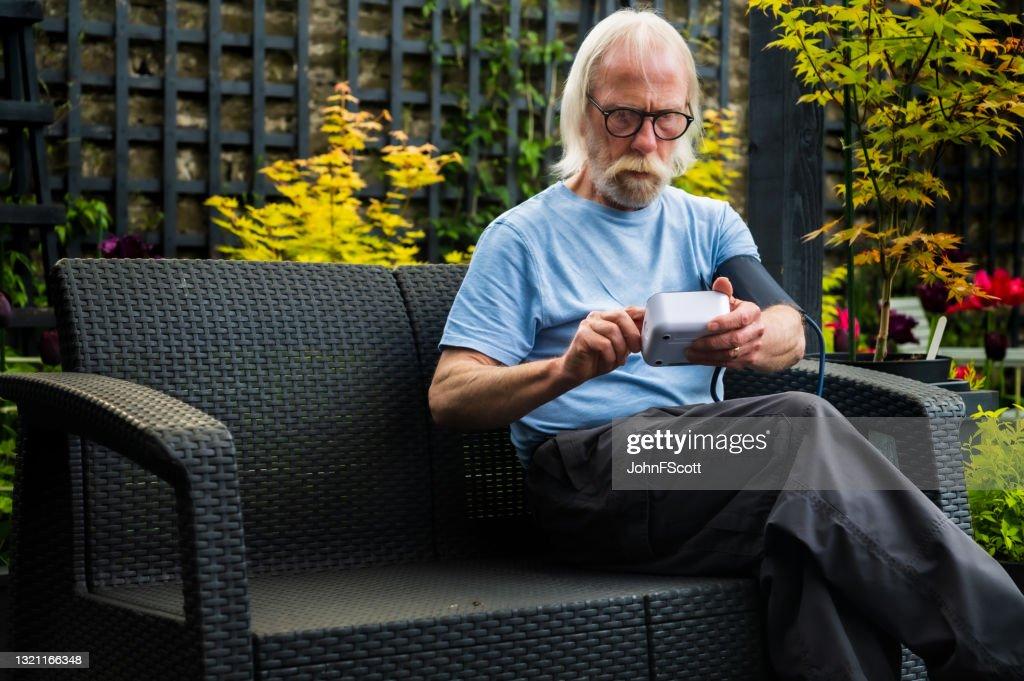 Senior man self checking blood pressure : Stock Photo