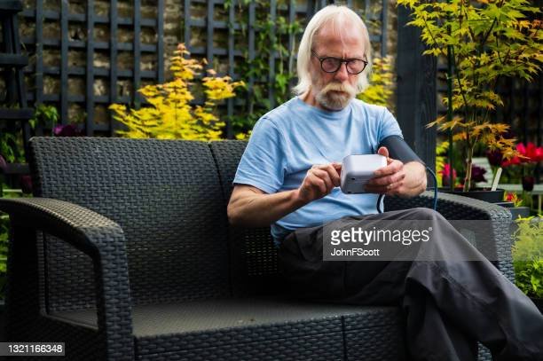 senior man self checking blood pressure - johnfscott stock pictures, royalty-free photos & images