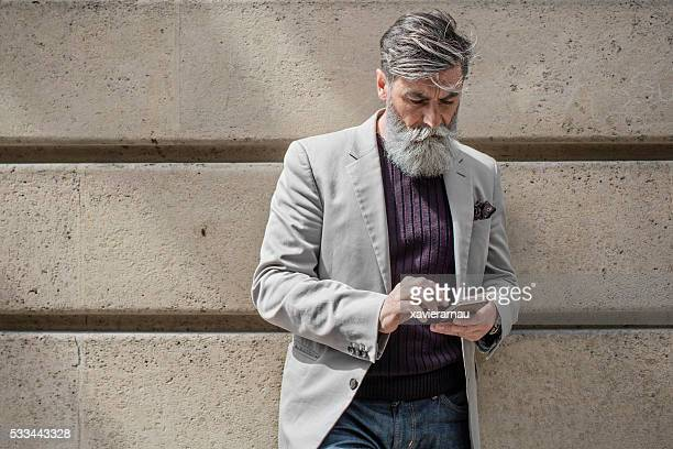 senior man sending a mobile phone message - metrosexual stock pictures, royalty-free photos & images