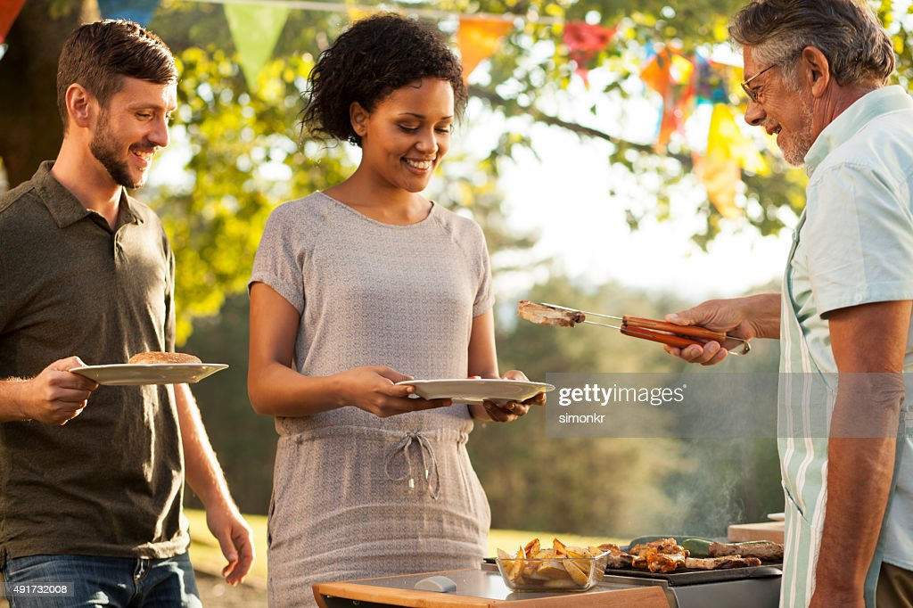 Senior man serving grilled meat to his son and daughter-in-law : Stock Photo