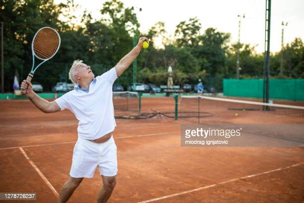 senior man serving on tennis court - serving sport stock pictures, royalty-free photos & images
