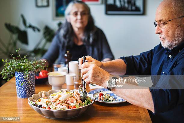 Senior man serving salad for himself while sitting with woman at table